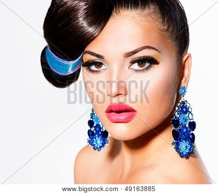 Fashion Model Girl Portrait with Brown Eyes and Blue Earrings. Creative Hairstyle. Hairdo. Make up. Beauty Woman isolated on a White Background