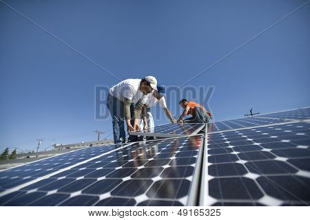 Interracial engineers placing solar panel against clear blue sky