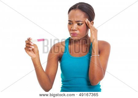 confused african woman looking at pregnancy test isolated on white