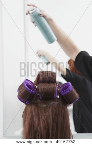 Rear view of woman with rollers getting hairsprayed by hairdresser in salon