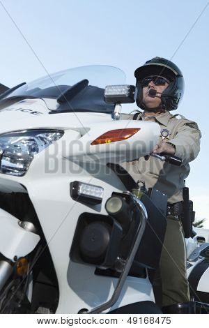 Low angle view of middle aged traffic cop sitting on bike against sky