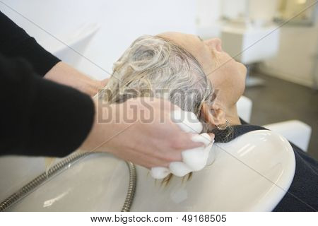 Senior woman getting hair washed by hairstylist in parlor