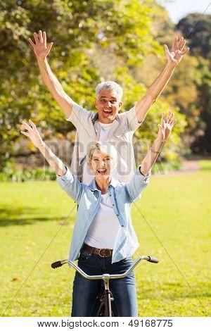 feliz casal sênior brincalhão divertir-se bicicleta de andar ao ar livre