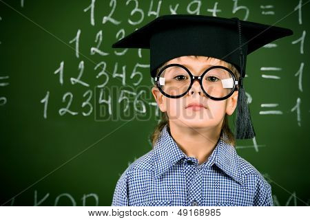 Portrait of a boy in round glasses and academic hat standing near the blackboard in a classroom.