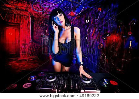 Beautiful sexy DJ girl working on a party in the old garage.
