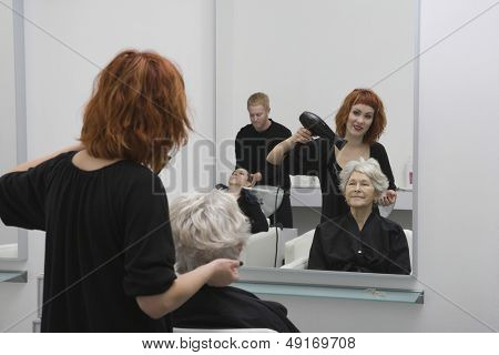 Happy female stylist blow drying senior woman's hair in salon