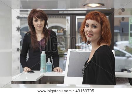Portrait of young female owner with customer purchasing hair products in salon