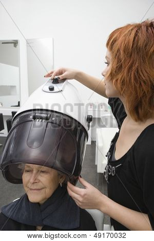Senior woman under hooded hair dryer while stylist adjusting dial of it