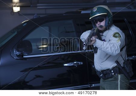 Confident traffic cop aiming rifle while standing against car