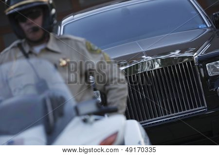 Middle aged traffic cop sitting on motorbike with car in background