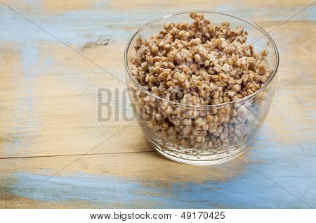 glass bowl of cooked buckwheat kasha on wood background