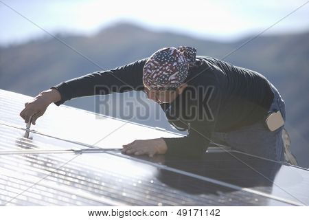 Middle aged engineer fixing solar panel on rooftop