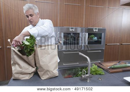 Male chef unpacking groceries from paper bags in commercial kitchen