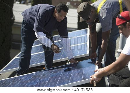 Multietchinc engineers placing solar panel together on rooftop