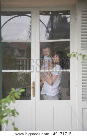 Side view of happy mother carrying baby in front of door