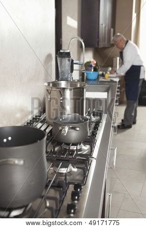 Closeup of utensils on stove with chef working in background at commercial kitchen