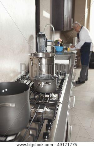 Closeup de utensilios de cocina con el chef trabajando en segundo plano en la cocina comercial