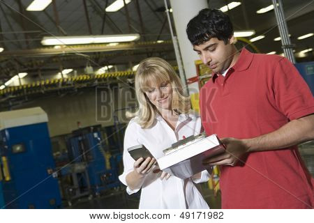 Young male and female make inventory in the newspaper factory