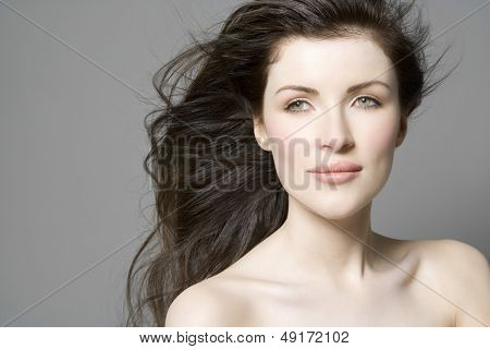Closeup portrait of a beautiful woman with long hair against gray background