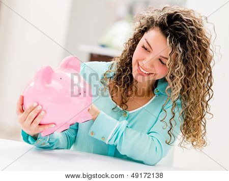 Happy woman holding a piggybank and smiling
