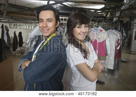 Portrait of confident coworkers standing arms crossed in laundry