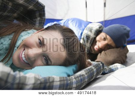 Portrait of a smiling young couple lying in sleeping bags in tent