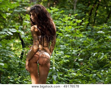 Charming woman sexy serious background dark forest
