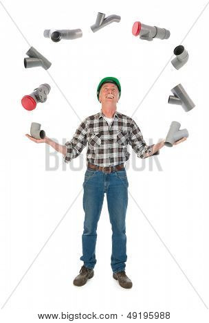 Funny plumber juggling with PVC tubes over white background