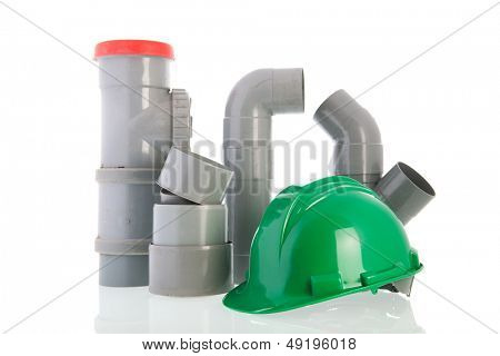 PVC pipes and tubes with green helmet isolated over white background