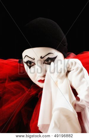 Mime actor dressed as Pierrot crying with a hanky