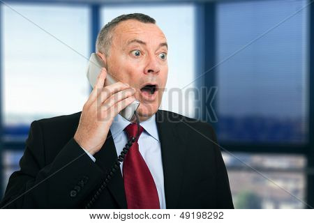 Portrait of a surprised businessman talking on the phone