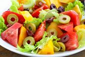 foto of rocket salad  - salad of colorful tomatoes and olives on the wooden table - JPG