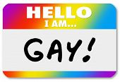 stock photo of homosexual  - Hello I Am Gay words on a nametag sticker to come out as a homosexual and announce your persuasion with pride to others - JPG