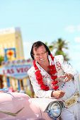 Elvis impersonator and Las Vegas on the strip pointing looking at camera in front of Welcome to Fabu