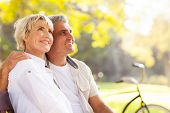 stock photo of bench  - elegant mature couple sitting on a bench outdoors - JPG