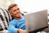 Handsome young man using laptop at home, sitting in armchair, smiling.