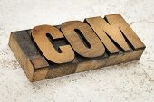 dot com - commercial internet domain in vintage letterpress wood type on ceramic tile background