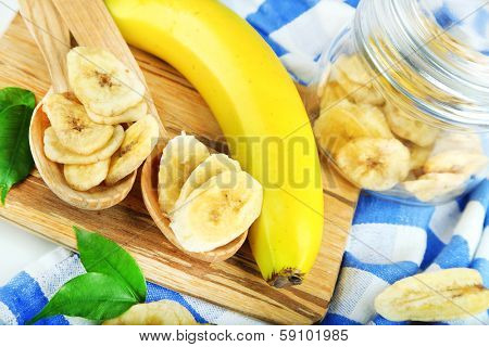 Fresh and dried banana slices in glass jar, on cutting board, close up