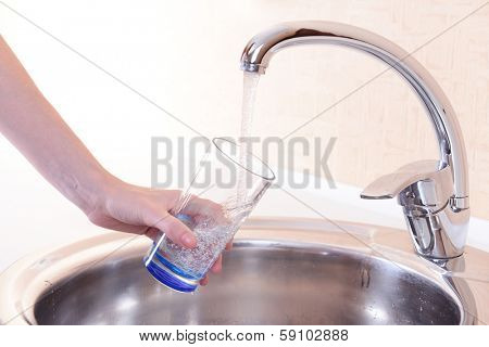 Hand holding  glass of water poured from  kitchen faucet