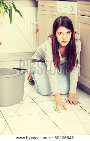 Young woman cleaning flor on her knees