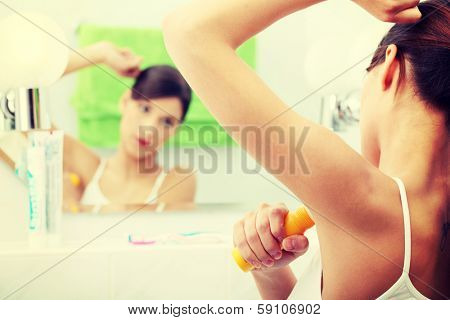 Young beautiful caucasian woman using deodorant at her bathroom