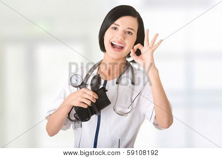Woman doctor with blood pressure gauge gesturing perfect