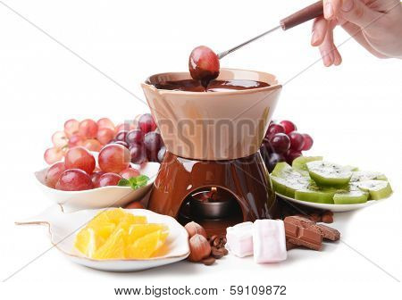 Chocolate fondue with marshmallow candies and fruits, isolated on white