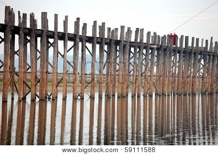 MANDALAY, MYANMAR - DECEMBER 10, 2013: Two monks are walking over U bein's Bridge in the early morning. U Bein's Bridge is ancient and it is made entirely from teak wood.