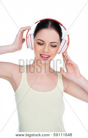 Happy young woman listening to music on a set of modern headphones as she smiles in appreciation, isolated on white