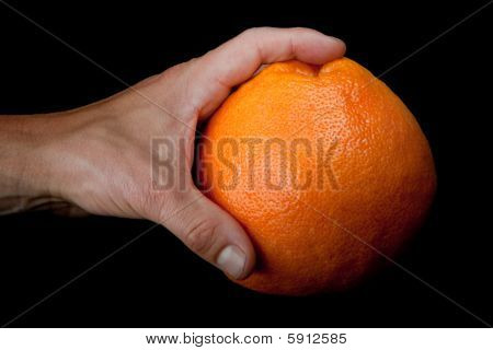 Male hand holding grapefruit over black background
