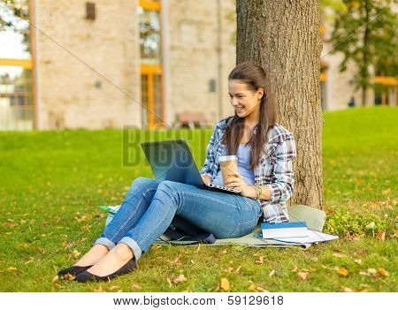 education, technology and internet concept - smiling teenager in eyeglasses with laptop computer and take away coffee or tea