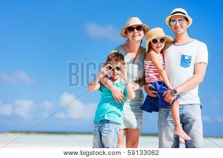 Happy beautiful family posing at beach during summer vacation