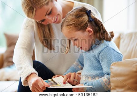 Mother And Daughter Reading Story At Home Together