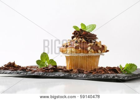 homemade muffin with chocolate icing served on a slate cutting board